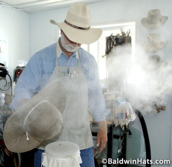 Steaming the hat shrinks the hat to a hat block that approximates the size and shape of the person's head.